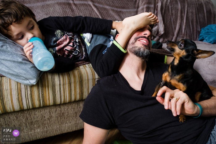 A little boy puts his foot on his father's face while he holds their small dog in this photograph by a Sao Paulo, Brazil documentary family photographer.