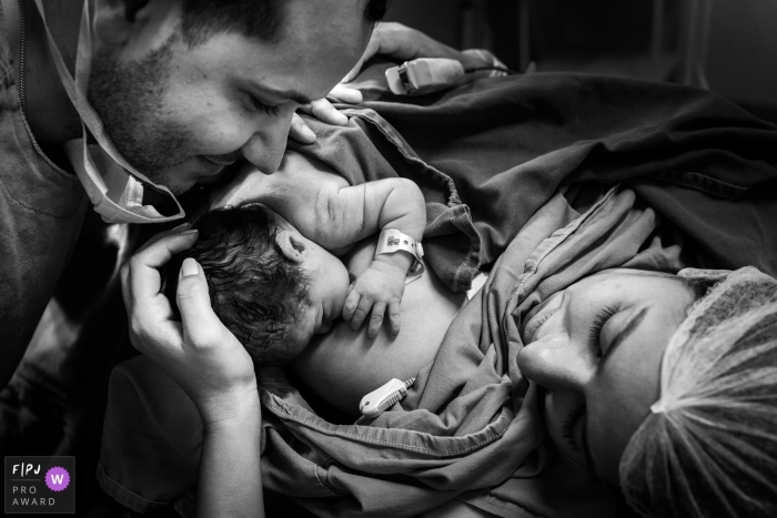 This black and white photo of a mother and father admiring their newborn was captured by a Brazil documentary family photographer.
