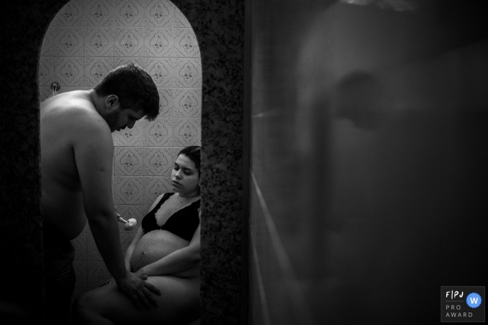 Brazil documentary family photographer captured this black and white photo of a husband and wife trying to relieve some pain in the shower during a home birth
