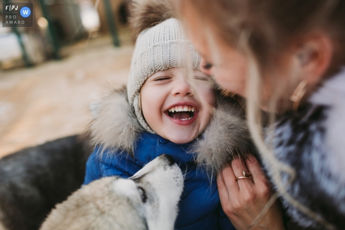 A mother holds her son while he laughs as a dog sniffs him in this documentary-style family image recorded by a Saint Petersburg, Russia photographer.