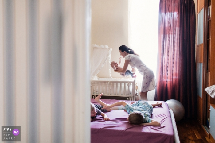 A mother lifts her baby out of his crib while her two other sons play on a bed in this Family Photojournalist Association contest awarded photo created by a Saint Petersburg, Russia family photographer.