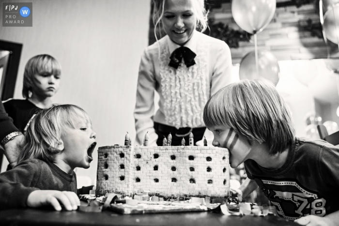 Two little boys eat a birthday cake without cutting it in this FPJA award-winning picture by a Saint Petersburg, Russia family photographer.