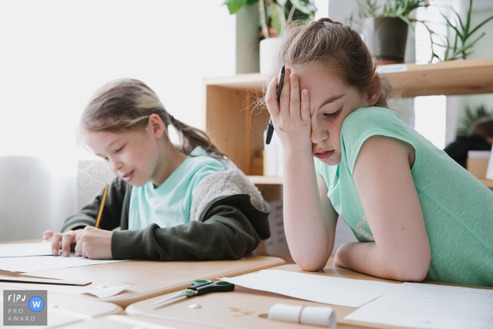 Two little girls try to concentrate on a school project in this Family Photojournalist Association awarded photo by a Saint Petersburg, Russia documentary family photographer.