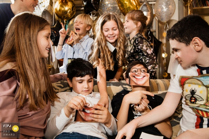 Children play and laugh during a birthday party in this FPJA award-winning image captured by a Saint Petersburg, Russia family photographer.
