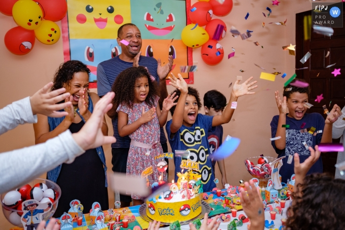 Children celebrate around a birthday cake in this image created by a Rio de Janeiro, Brazil family photographer.