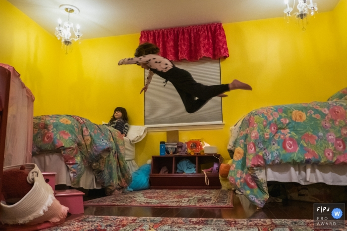 A girl leaps from her bed onto her sister's in this award-winning photo by a Los Angeles, CA family photographer.
