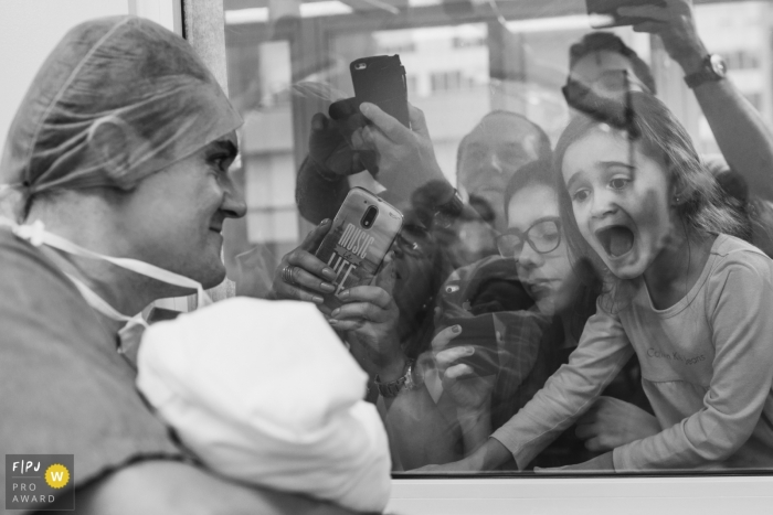 A family excitedly takes pictures through the hospital window as a nurse holds up their newest family member in this photo by a Sao Paulo, Brazil documentary birth photographer.