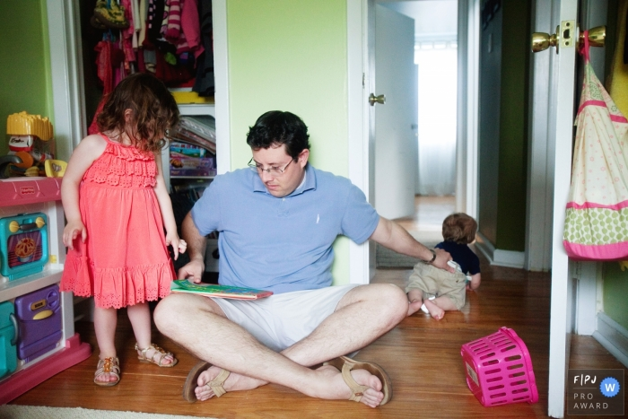 A father holds onto his son who tries to crawl out of the room as he tries to read to his daughter in this Family Photojournalist Association contest awarded photo created by a Philadelphia family photographer.