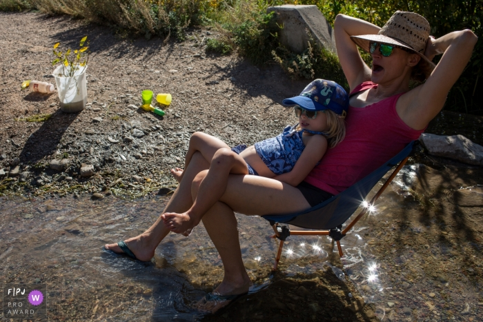 A little girl sits on her mother's lap as they sit in a small stream in this FPJA award-winning picture by a Boulder, CO family photographer.