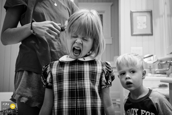 A girl shouts as her mother does her hair in this photo recorded by a Key West, FL award-winning, documentary-style family photographer.