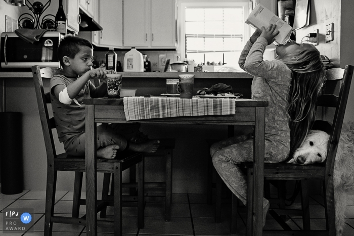 A boy and girl eat breakfast together as their dog licks the girl's seat for crumbs in this picture captured by a Key West, FL family photojournalist.