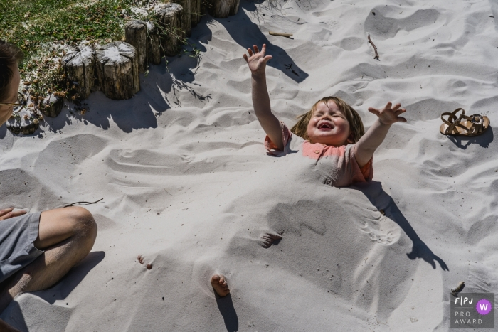 Flanders girl getting buried by dad at the beach - Limburg family photography session