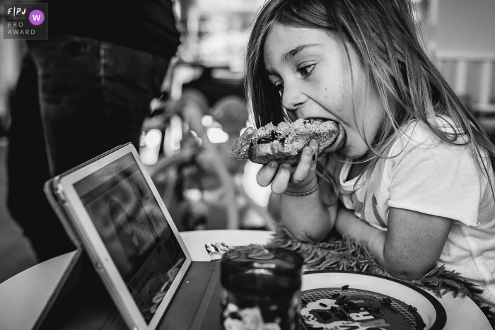 Noord Brabant family photography | Black and white photo of a young girl watching an iPad as she eats a meal