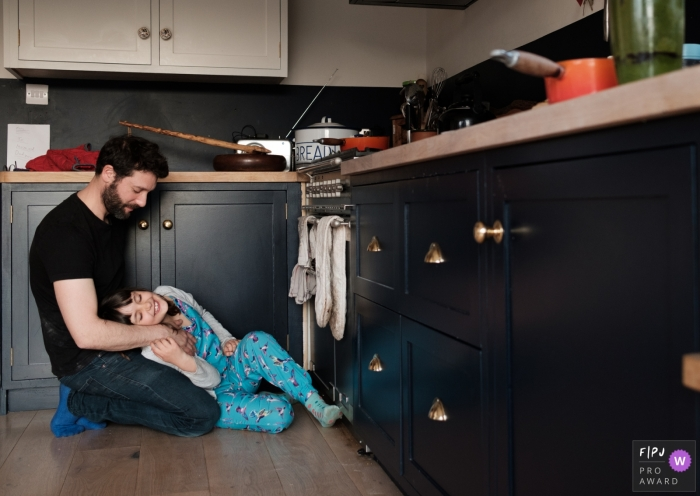 UK Family Photographer | Girl cuddles with her dad on the kitchen floor