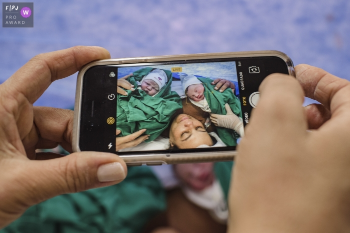 Brazil detail photo of dad's phone screen showing mom with twin babies after delivering in Rio de Janeiro hospital.