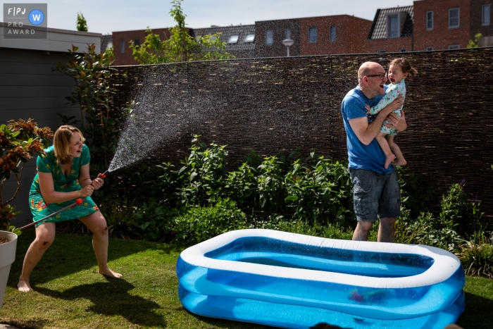 Noord Holland documentary family photographer for Netherlands - Playing games with water is always fun!