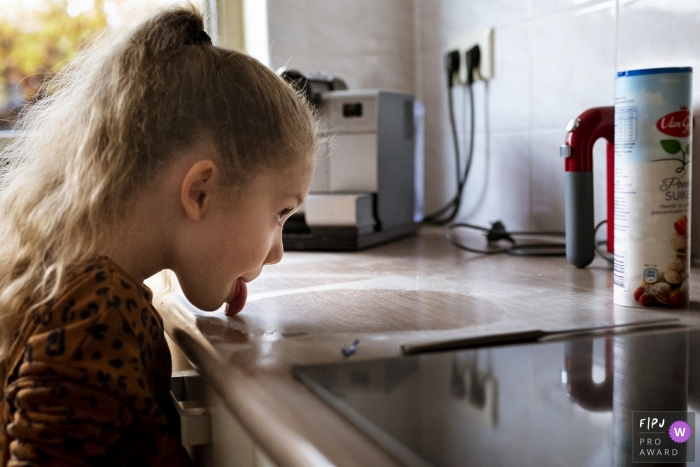 Noord Holland, Netherlands documentary-style photo of young girl licking sugar off the kitchen counter.