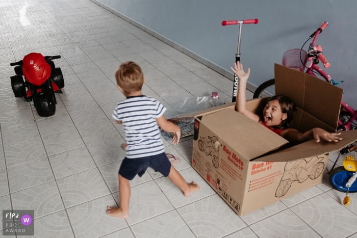 Brazil Child and Family Photographer  | Brothers playing at home. Boy after receiving a birthday present, is surprised by his sister who hides inside the toy box.