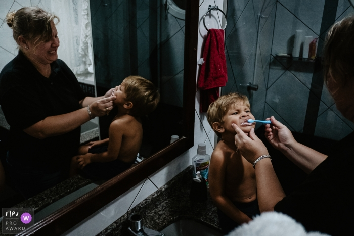 Florianopolis Day in the Life Photographer | Mother brushing her son's teeth in the bathroom of their home.