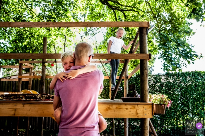 Gelderland documentary family photography - Netherlands child seeking comfort with dad after a little brother-sister-fight