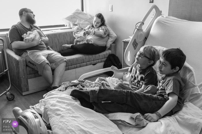 Connecticut Family and Birth Photography | The newness of their new twin sisters has worn off and two big brothers take over Mom's hospital bed to watch TV while Mom & Dad care for the babies in the background.