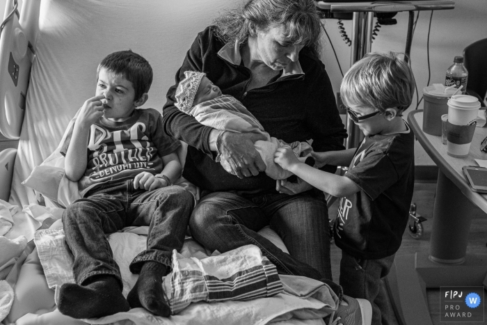 Connecticut birthing photography - Kids will be kids. One big brother checks out his baby sister's feet, while the other picks his nose on the hospital bed.