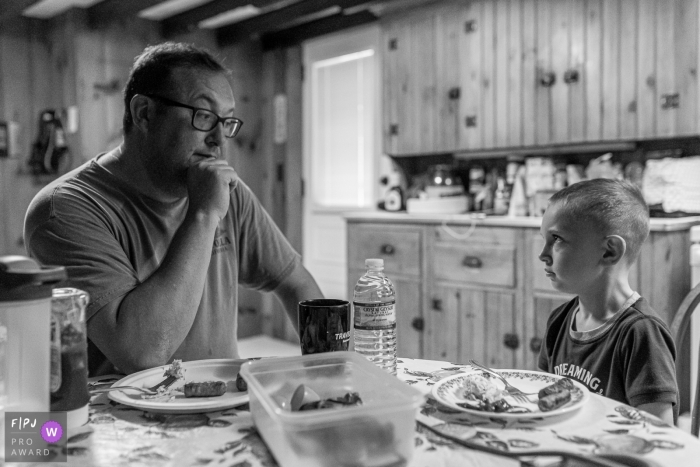 """Connecticut family photojournalism session in home - Dad gives his son """"the look"""" during breakfast."""