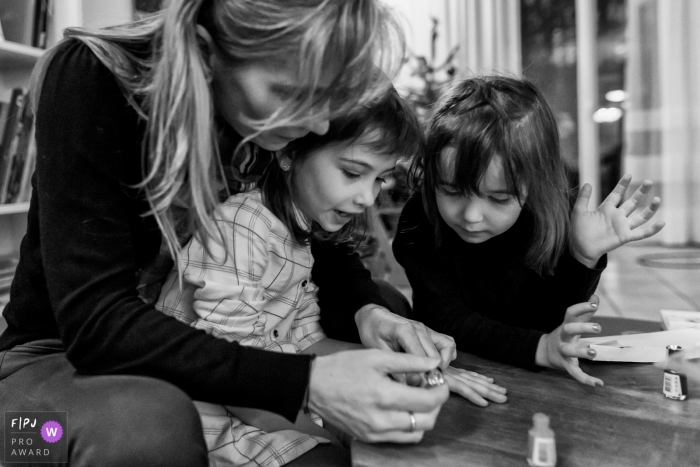 France Family Photographer | Mother spends time with her girls while they apply nail polish.