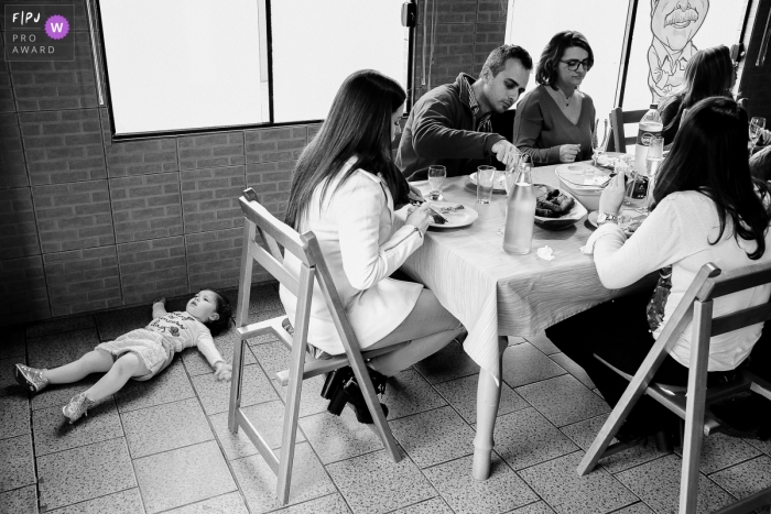 Rio Grande do Sul Family photography of a child lying on the floor as the family has lunch at the table.