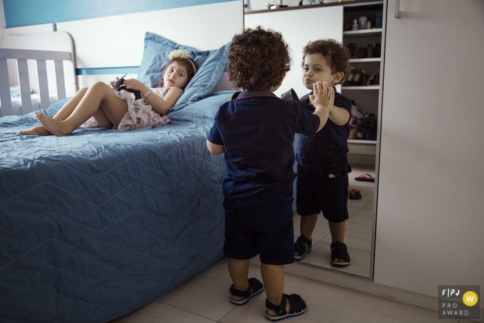 Rio Grande do Sul family photographer for Brazil - A young boy is Figuring out the mirror.