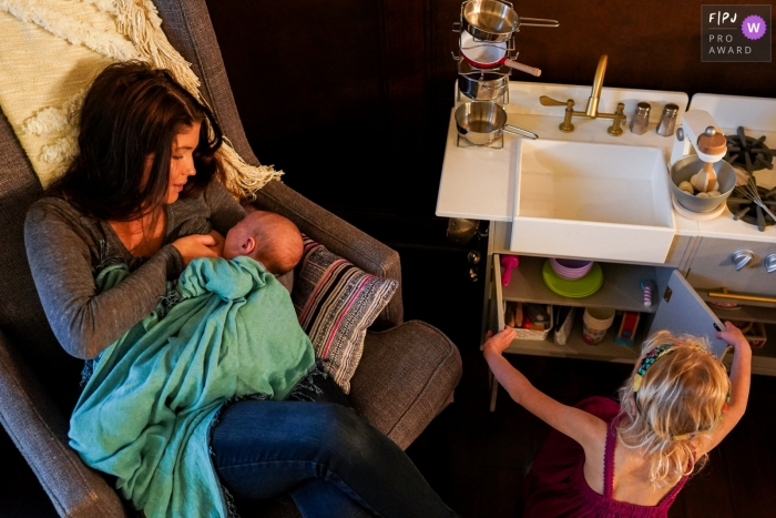 Washington momma breastfeeds while daughter plans to bake on her easy bake oven during a Seattle day in the life photo session.