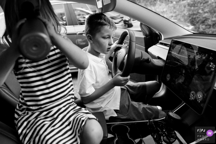 Seattle kids playing while driving a video game on a Tesla - WA family photographer