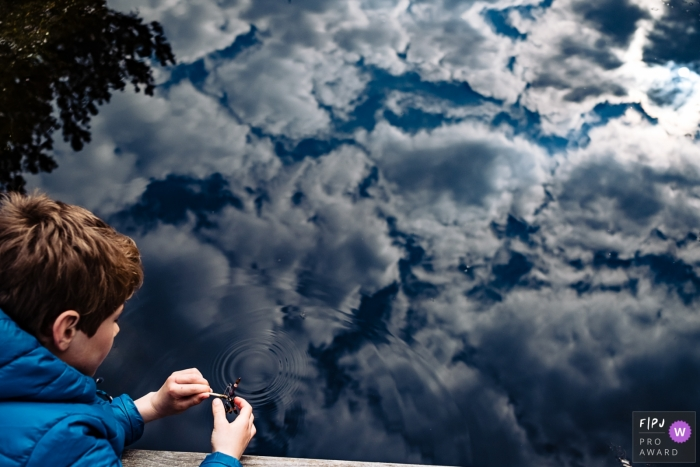 Boy plays by the water with a beautiful reflection of sky and clouds | Belgium Family Photo