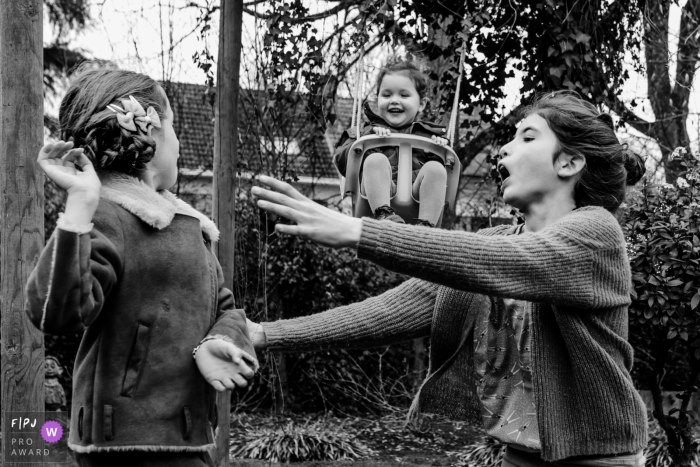 Flanders Family Photography | children pay in the backyard while young one swings