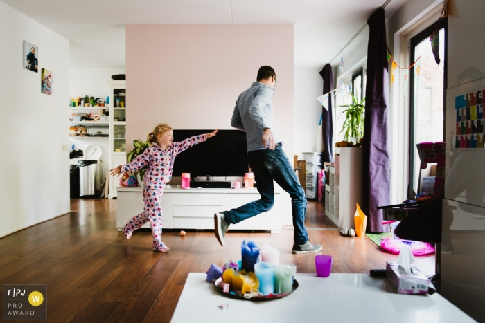 Amsterdam family photoshoot session with girl chasing around dad in the house.