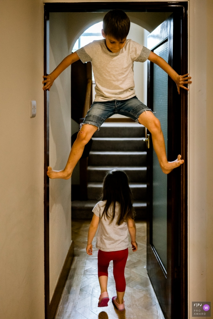 Kent	Boy climbing a doorway with girl walking under during family photo session at home in England.