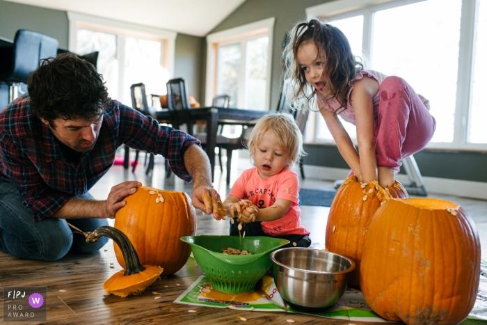 Family carves pumpkins as girl climbs into pumpkin | Kingston Family Photography