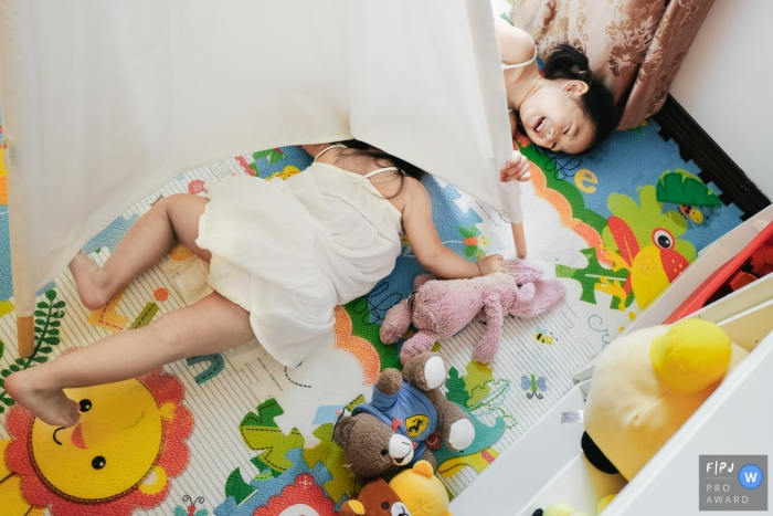 Two sisters are playing hide and seek | Family Photography in China