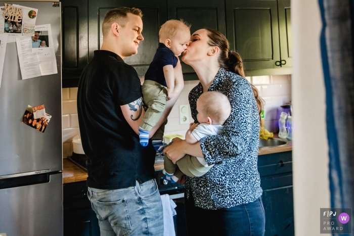 Netherlands family photo session - A moment with twins, in the kitchen, with a kiss from mom.