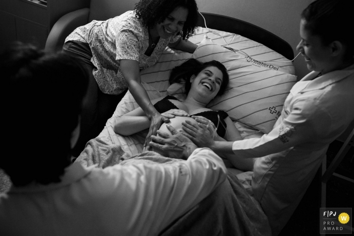 Minas Gerais mom-to-be in labor receiving affection from her medical team | Minas Gerais birthing photography session.