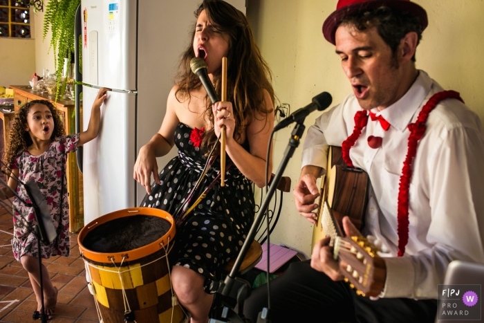 Minas Gerais excited singing girl with musicians couple - Family party photography for Brazil.