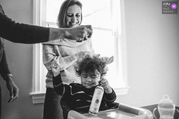Washington DC family photo session | Dad is spraying his son's hair during his breakfast.