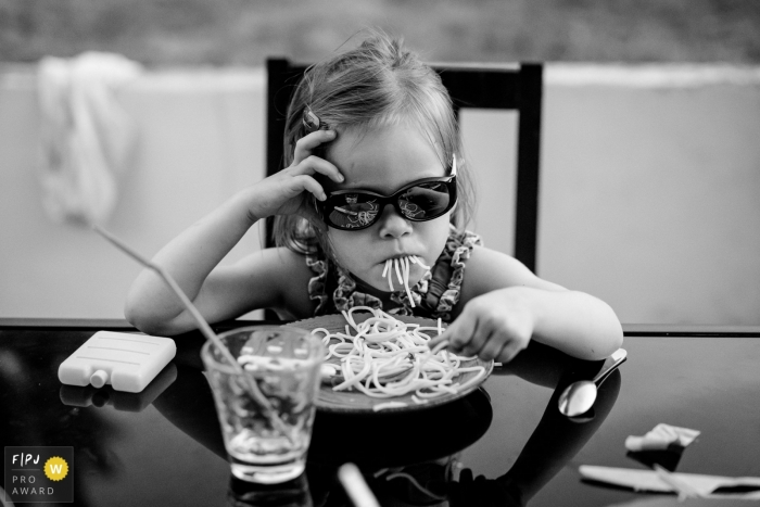 A little girl eat pasta with her sunglasses   France child photography