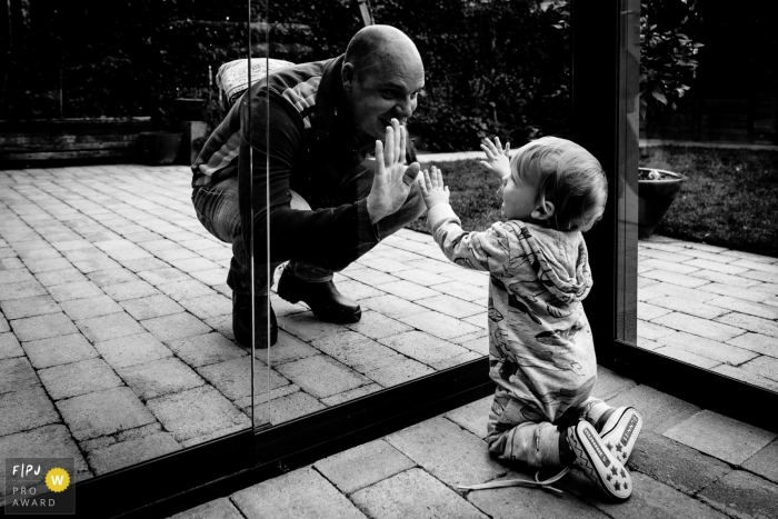 Father and son play with glass doors separating them | Drenthe Family Photography
