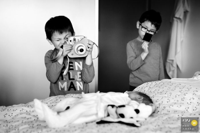 Allier family photo session with big brothers taking pictures of new baby on the bed.