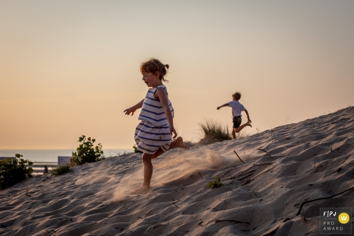 Siblings play at the beach running through sand | East Flanders Family Photography