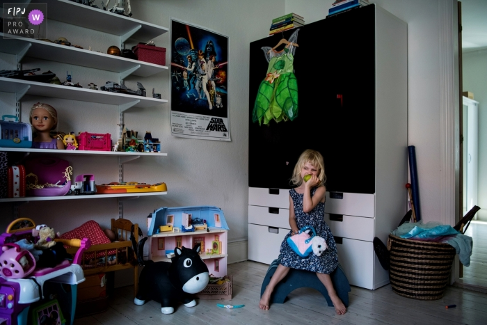Copenhagen Denmark young girl alone in her room with toys - In home family pictures - DITL