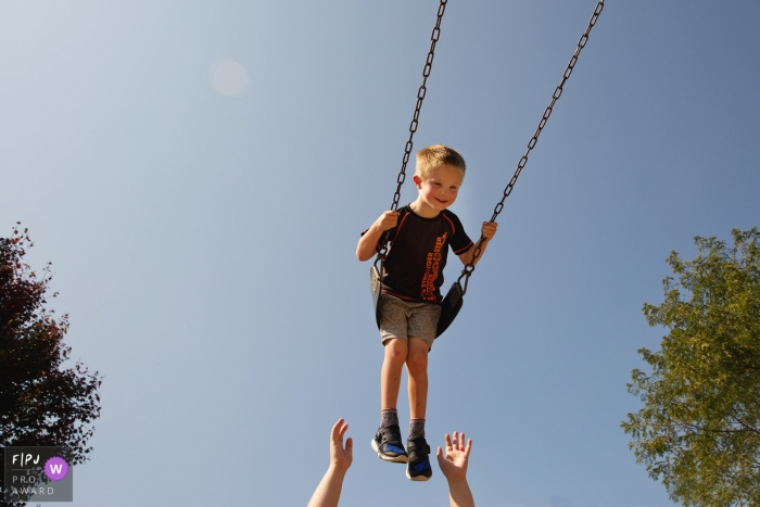 State College Pennsylvania boy in a swing - PA family photo session outside at the park.
