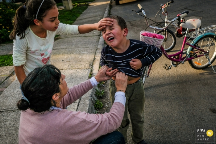 Boy is cries to his mother and sister while in pain after what appears to be a bicycle accident | Talca Family Photographer