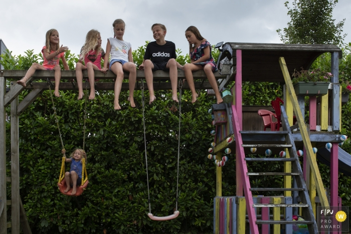 Kids sit up on the top of playground equipment | Breda Family Photography